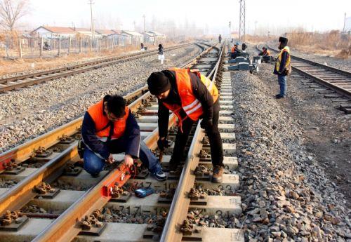 工长姜鹏,青年职工杨赫在检查测试轨道电路绝缘.