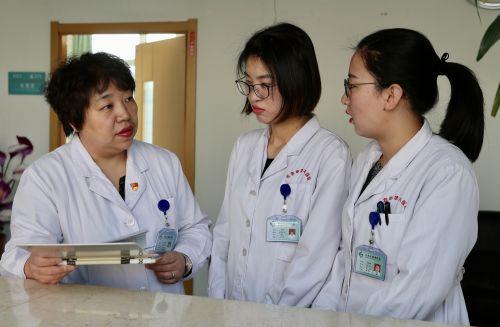 图为燕利娟主任正在与科室医生探讨患者治疗方案