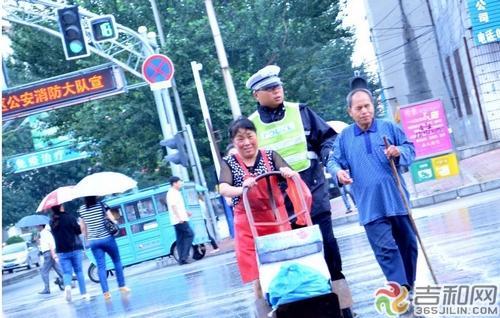 四平/路子博在雨中搀扶盲人过马路 网络截图