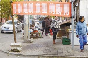 长春市万宝街一条横幅挂得过低 引无数路人尽弯腰